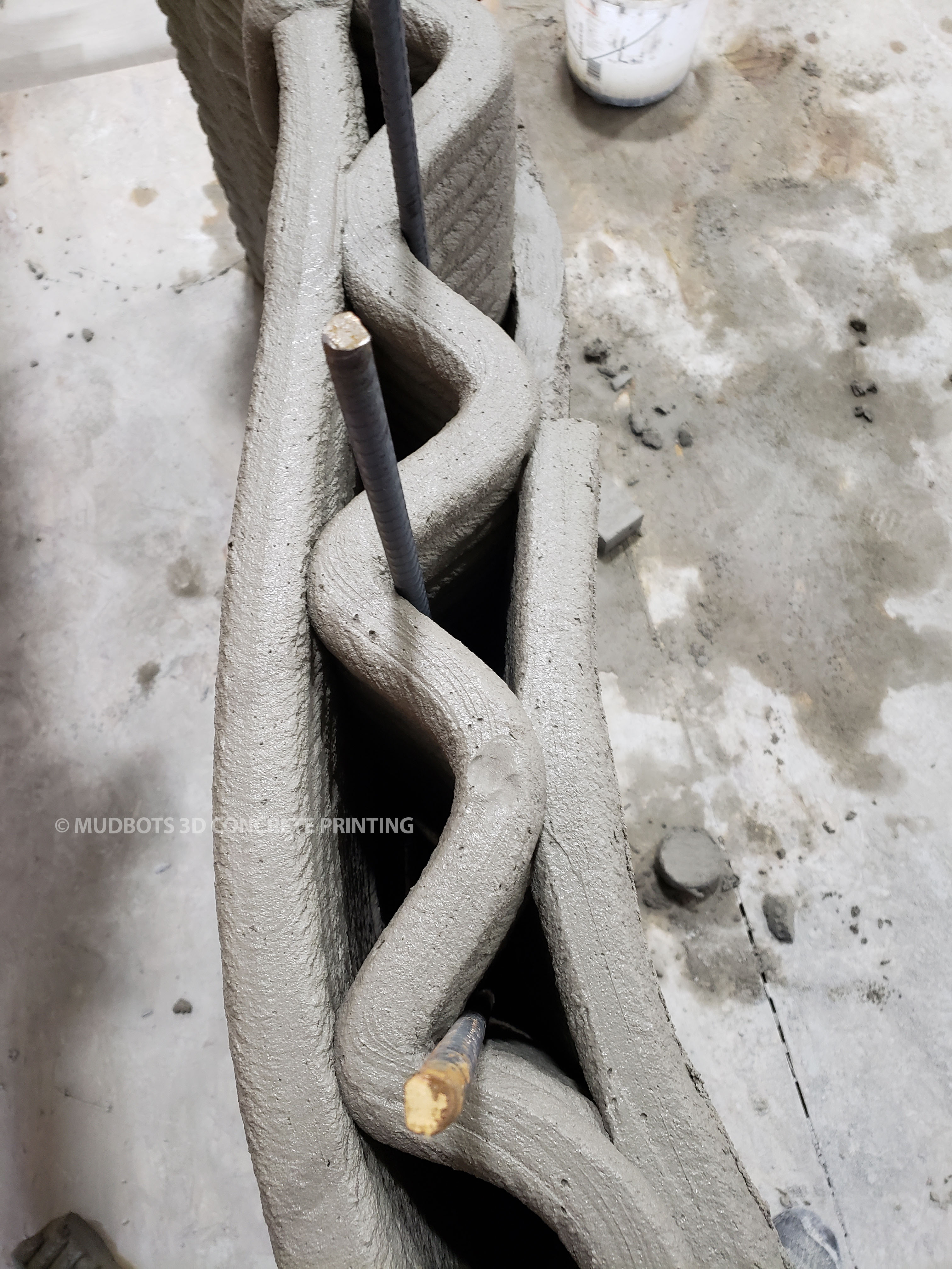 Top view of 3D printing concrete around rebars for a stronger foundation.