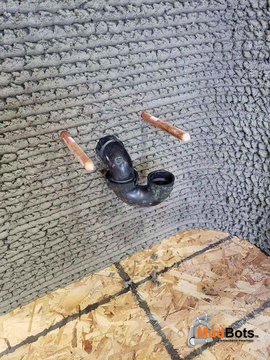 A close up of plumbing installed on 3D printed layer by layer concrete wall